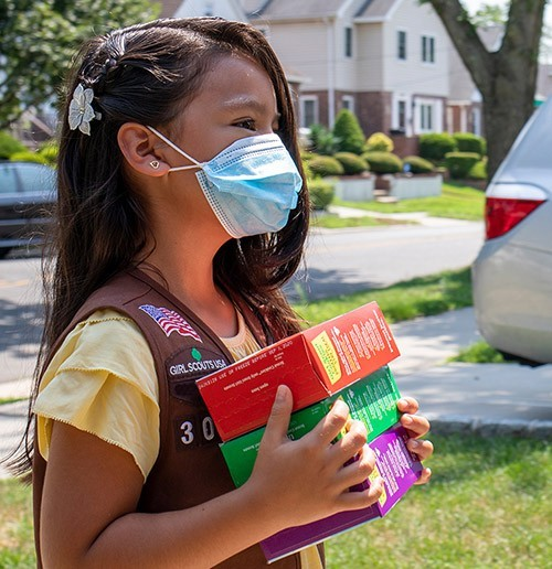 A girl scout with a mask delivery cookies.