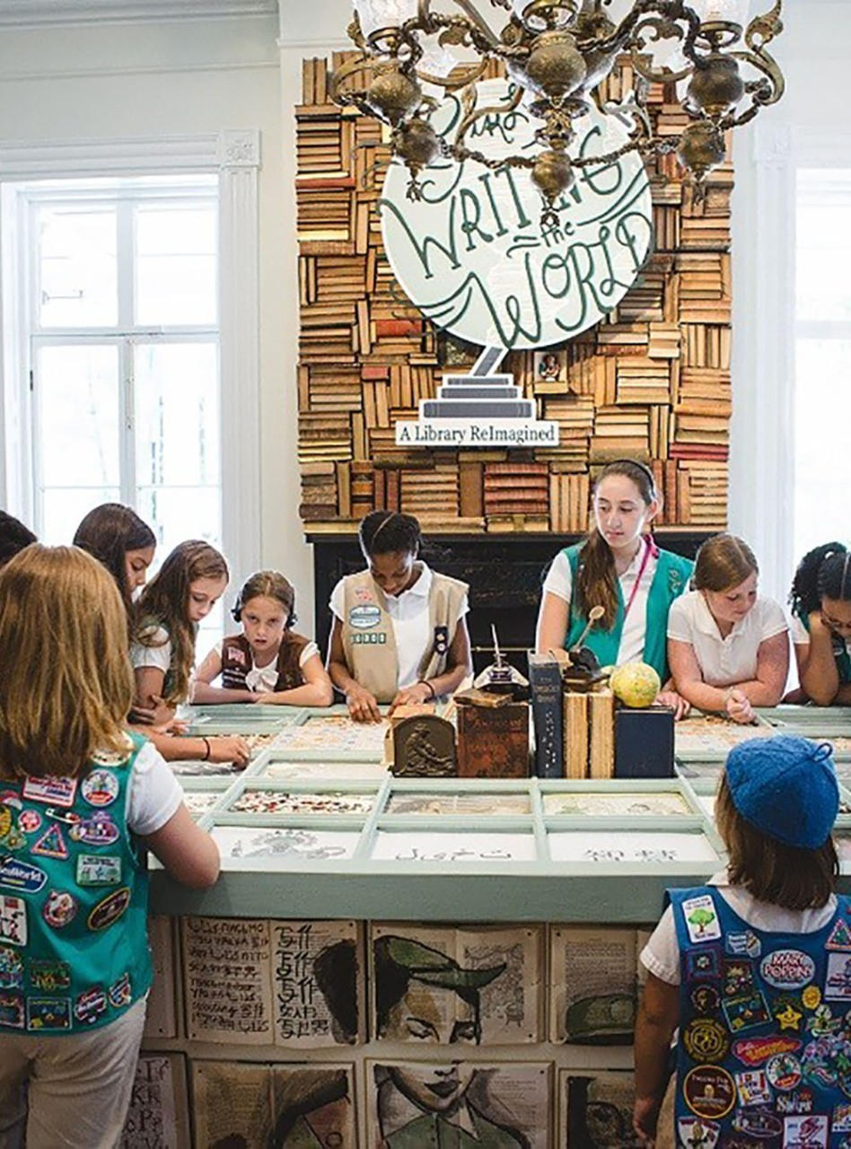 A group of Girl Scouts examine Girl Scout artifacts.