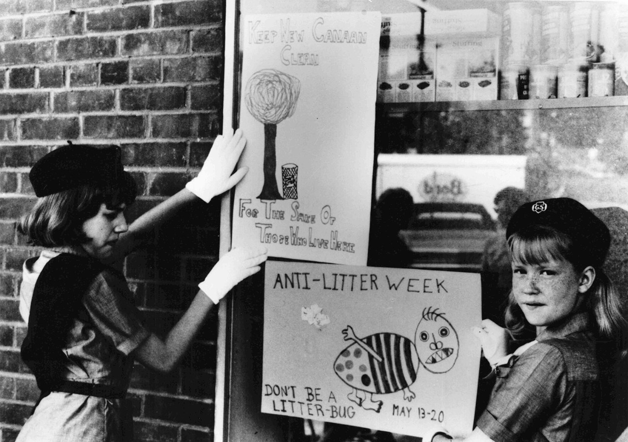 Girl Scouts hang anti-littering posters on shop window, 1976