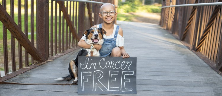 Sarah celebrates being cancer free with her dog.