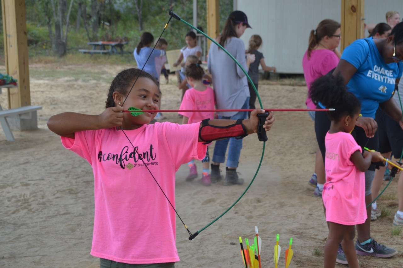 Daisy Girl Scout confidently tries her hand at archery.