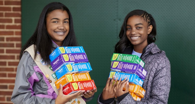 Smiling Girl Scout Holds Cookie Boxes