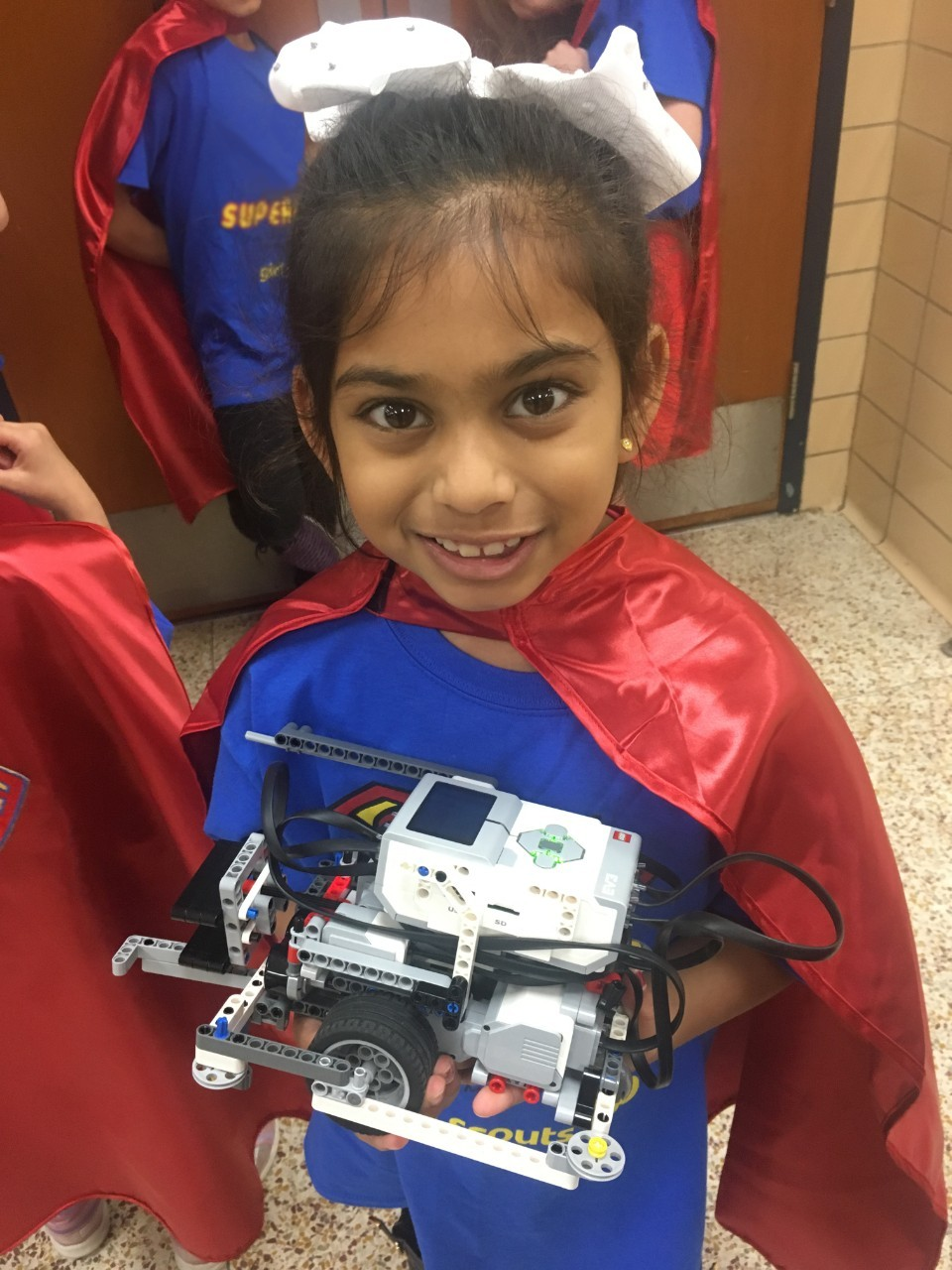 Supergirl Pari proudly holds one of her team's robots.