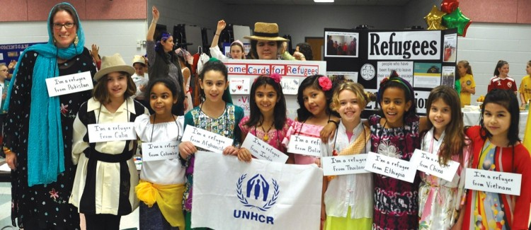 Troop 3173 holds UNHCR flag at World Thinking Day event.