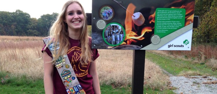 Girl Scout smiles big by the sign she made for the first-ever official Girl Scout hiking trail