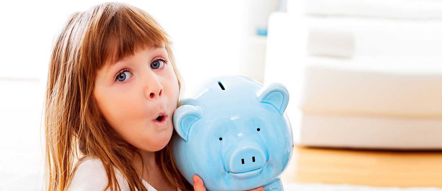 little girl learning about money with her piggy bank