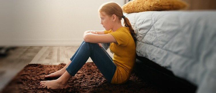 girl sitting on floor in her bedroom upset because coronavirus cancelled everything