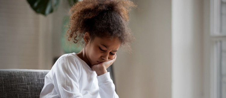 Girl in white shirt resting her head on her hand looking anxious and depressed