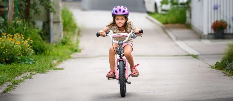 young girl in a purple helmet riding a bike