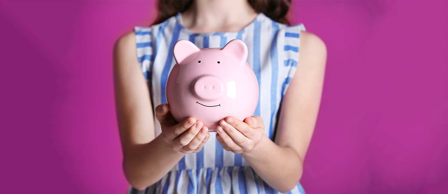 photo of girl holding piggy bank to illustrate the student debt gender gap