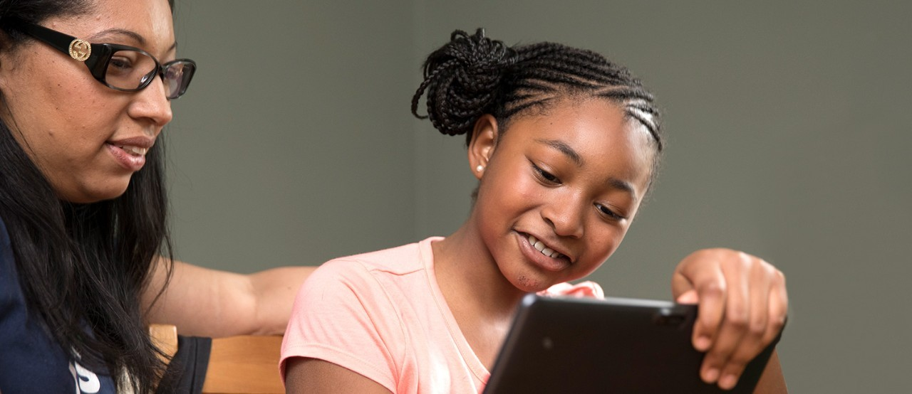 A young girl and mother doing a distance learning activity