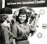 Photo of Girl Scouts in front of International Friendship poster. © GSUSA. All rights reserved.