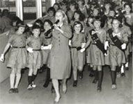 Photo of Debbie Reynolds standing with Girl Scouts. © GSUSA. All rights reserved.